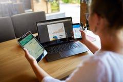 Gemengde rasvrouw in glazen die met veelvoudige elektronische Internet-apparaten werken De Freelanceronderneemster heeft tablet e royalty-vrije stock foto