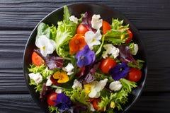 Gemengde salade van eetbare bloemen met sla, tomaten en room c royalty-vrije stock foto's