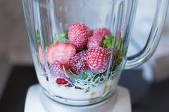 Gemengde verse smoothies van spinazie en aardbeien in een mixer royalty-vrije stock afbeelding
