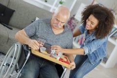 Gemenskapsjuksköterska med den gamla rörelsehindrade mannen på rullstolen arkivbilder