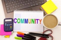 Gemenskaptext i kontoret med omgivning liksom bärbara datorn, markör, penna, brevpapper, kaffe Affärsidé för samhörighetskänsla arkivfoto