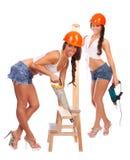 Gemini girls in orange helmets with a saw Stock Photo