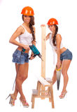 Gemini girls in orange helmets with a saw Royalty Free Stock Photography