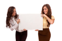 Gemini Sisters Hold A Poster On A White Background Royalty Free Stock Photography
