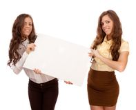 Gemini sisters hold a poster on a white background Stock Photos