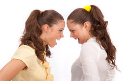 Gemini sisters quarrel on a white background. Stock Photo