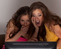 Gemini sisters watching a horror movie on TV. Their faces distorted with fear Stock Images