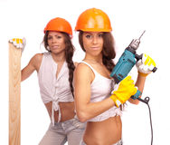 Gemini Sisters With An Electric Drill Royalty Free Stock Images