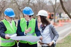 Gemischte Gruppe Architekten und Teilhaber, die Projektdetails über eine Baustelle besprechen stockfotografie