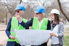 Gemischte Gruppe Architekten und Teilhaber, die Projektdetails während der Inspektion einer Baustelle besprechen lizenzfreie stockfotos