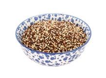 Gemischte rote, weiße und schwarze Quinoa in einer blauen und weißen Porzellanschüssel Stockbilder
