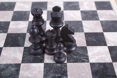 Gemischte schwarze hölzerne chesspieces auf Schachbrett Lizenzfreie Stockbilder