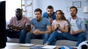 Gemischtrassige Freunde, die auf Couch und bequem aufpassendem Sportspiel im Fernsehen sitzen lizenzfreies stockbild