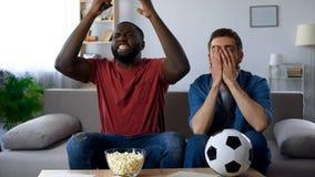 Gemischtrassige Freunde, die auf der Couch und aufpassendem Spiel, enttäuscht über Ergebnis sitzen lizenzfreies stockbild