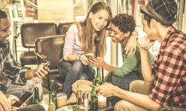 Gemischtrassige Freunde, die Bier trinken und Spaß mit Handy haben Stockbild