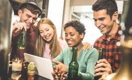 Gemischtrassige Freunde, die Bier trinken und Spaß mit Tablette haben Lizenzfreie Stockbilder
