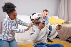 Gemischtrassige Gruppe Freunde, die den Spaß versucht auf Schutzbrillen der virtuellen Realität 3D haben stockfotografie