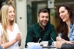 Gemischtrassige Gruppe Freunde, die einen Kaffee zusammen trinken stockfotos