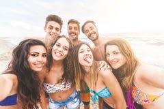 Gemischtrassige Gruppe Freunde, die selfie auf dem Strand nehmen stockfoto