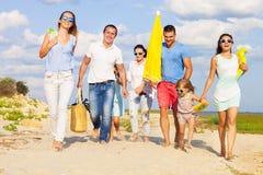 Gemischtrassige Gruppe Freunde mit den Kindern, die am Strand gehen stockbilder