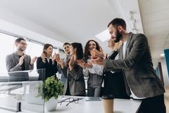 Gemischtrassige Gruppe Geschäftsleute, die Hände klatschen, um ihren Chef zu beglückwünschen - Unternehmensteam, Stehbeifall nach lizenzfreies stockfoto