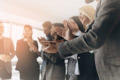 Gemischtrassige Gruppe Geschäftsleute, die Hände klatschen, um ihren Chef zu beglückwünschen - Unternehmensteam, Stehbeifall nach lizenzfreie stockfotografie