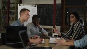 Gemischtrassige Gruppe Geschäftsleute, die im modernen hölzernen Innenbüro sich treffen Junger Teamholding-Unternehmensplan stock footage