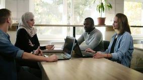 Gemischtrassige Gruppe Geschäftsleute, die im modernen hellen Büro am Holztisch sich treffen Junges Team, das theproject besprich stock video footage