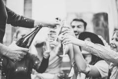 Gemischtrassige Gruppe junge Freunde, die Spa? Gl?ser Champagner auf Hochschultreppe trinkend und r?stend haben stockbilder