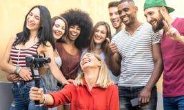 Gemischtrassige junge Freunde, die selfie mit beweglichem intelligentem Telefon- und Stabilisatorkardanring - Freundschaftskonzep stockfotos