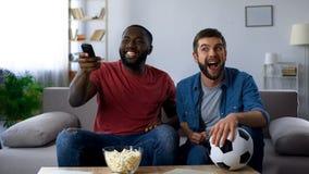 Gemischtrassige Kerle, die Fernsehen laut, Schluss des Fußballwettbewerbs mit Nationalmannschaft machen lizenzfreie stockfotos