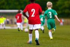Gemischtrassige Kinder, die Fußball auf dem Sportfeld treten stockfoto