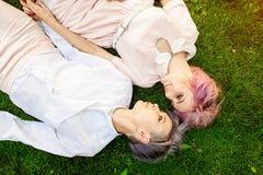 Gemischtrassige lesbische Paare, die auf dem Gras liegen Sie sind zwei junge Frauen, die am Park stillstehen lizenzfreie stockbilder