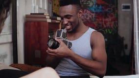 Gemischtrassige Paare in den Pyjamas auf dem Bett am Morgen Der junge Mann, der Fotos auf dem alten photocamera macht, Frau wirft Stockbild