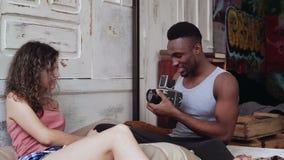 Gemischtrassige Paare in den Pyjamas auf dem Bett am Morgen Der junge Mann, der Fotos auf dem alten photocamera macht, Frau wirft Stockbilder
