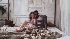 Gemischtrassige Paare in den Pyjamas, die auf Bett und Gebrauch Smartphone sitzen Afrikanischer Mann und europäische Frau, welche Stockfotografie