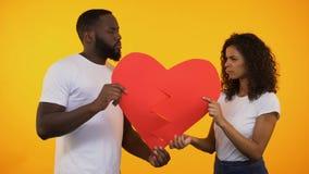 Gemischtrassige Paare, die zwei Teile Papierherz, Auseinanderbrechen-Verhältnis-Krise halten stock video footage