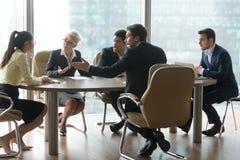 Gemischtrassige Teamgruppe, die im Bürositzungssaal bei der Sitzung diskutiert stockfotos