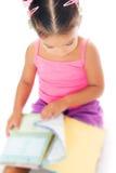 Gemischtrassiges kleines Mädchen, das ein Buch liest Stockfotografie