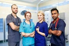 Gemischtrassiges Team von jungen Doktoren in einem Krankenhaus, das in einem Operationsraum steht Stockfotografie
