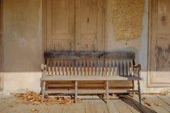 Gemischtwarenladenwand mit einer alten verwitterten Holzbank Stockfoto