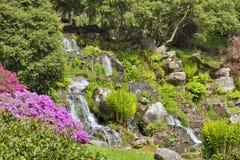 Gemodelleerde Engelse tuin met steenwaterval in de lente Royalty-vrije Stock Afbeelding