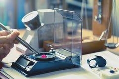 Gemologist som graderar ädelstenstenen för röd färg i gemologylaboratorium Arkivbilder