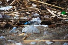 Gemorst huisvuil op het strand Lege gebruikte plastic fles royalty-vrije stock fotografie