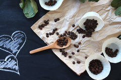 Gemorste koffiebonen op pakpapier op een zwarte lijst met harten Royalty-vrije Stock Foto's