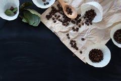 Gemorste koffiebonen op pakpapier op een zwarte lijst met harten Stock Fotografie