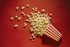 Gemorste popcorn op een rode achtergrond, een bioskoop, films en entertai stock afbeeldingen