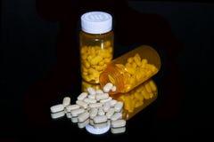 Gemorste witte pillen met oranje flessen op zwarte stock afbeeldingen