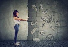 Gemotiveerde jonge vrouw die tegen verleiding van het eten van snelle voet en het kiezen van beter dieet verzetten zich stock afbeeldingen