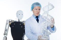 Gemotiveerde nauwkeurige mens die een 3D model van het genoom houden Royalty-vrije Stock Afbeeldingen